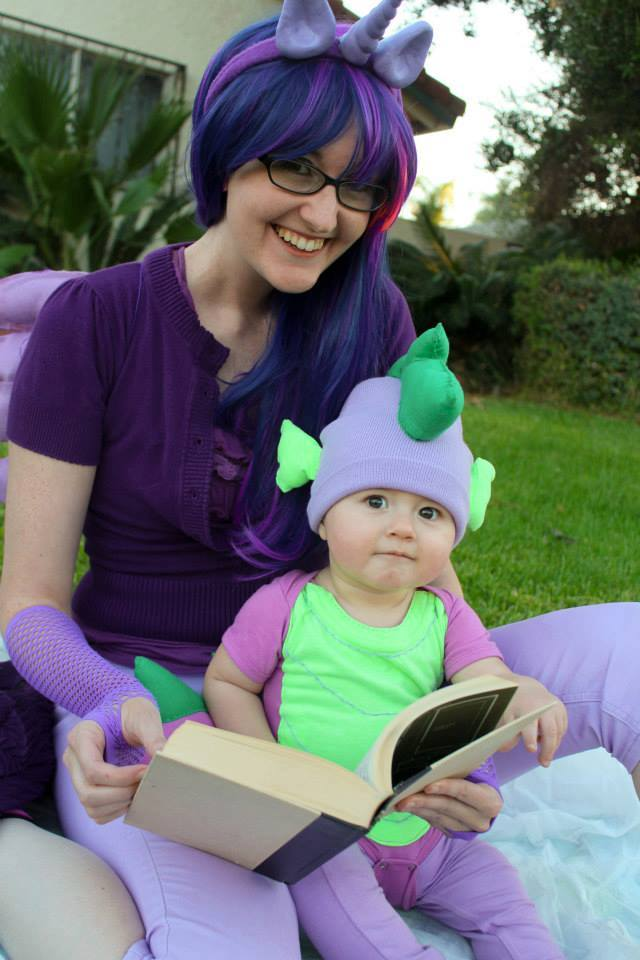 Laci Morgan cosplay as Twilight Sparkle, reading a book with a baby dressed in a Spike the Dragon costume