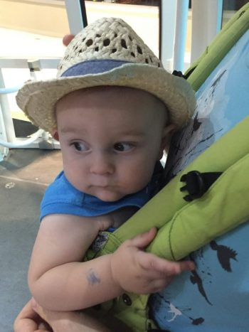 baby boy in a hat holding onto the straps of a green baby carrier