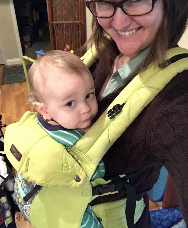 A baby seated in a green Lillebaby carrier, worn by his mom