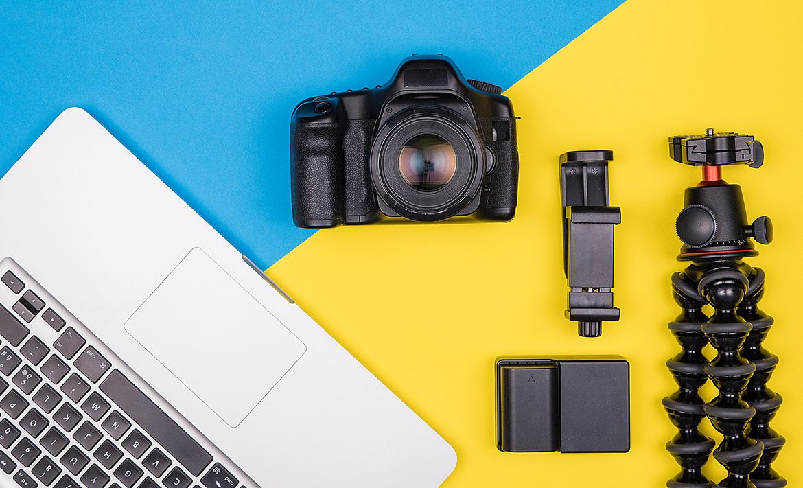 Camera with accessories next to a laptop on two colored background. Top view. Flat lay