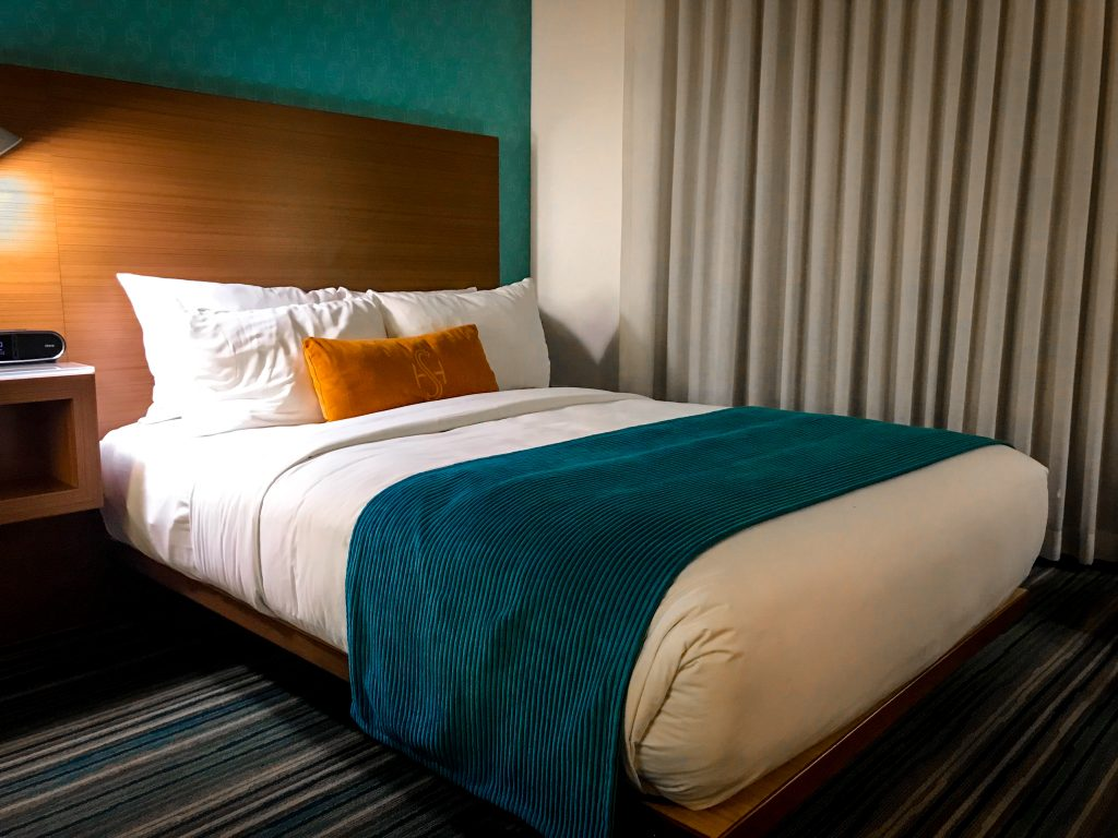 Double size bed with turquoise duvet cover and orange pillow at the Shore Hotel Santa Monica