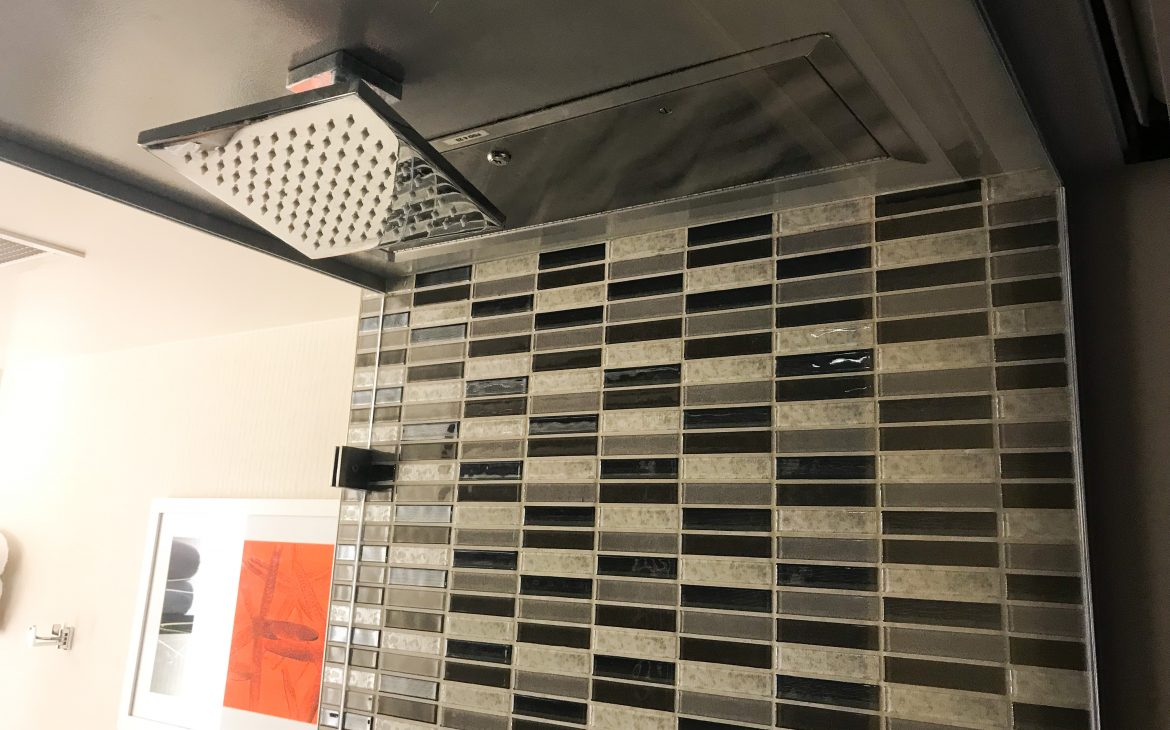 Tiled shower with rainfall showerhead at The Shore Hotel Santa Monica