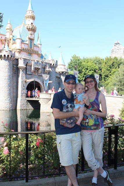 A family visiting Disneyland with their baby, standing in front of Sleeping Beauty's castle