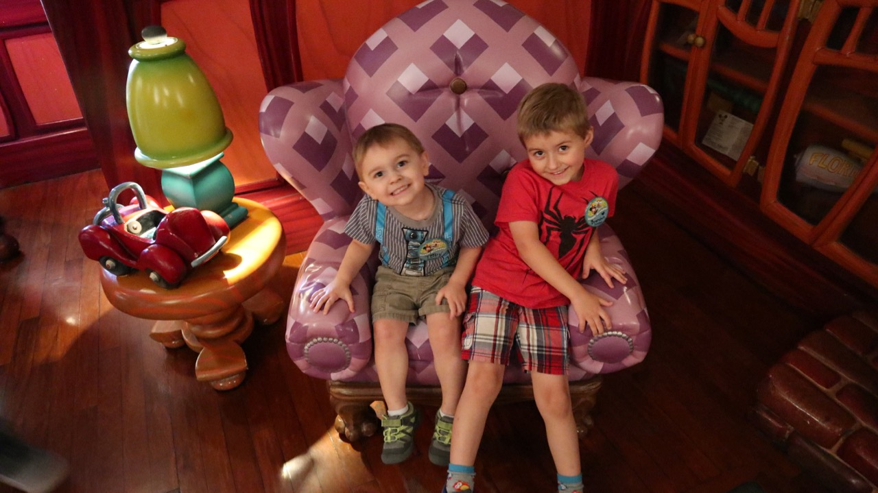 two smiling little boys sitting in a purple chair in Mickey's House in Toontown at Disneyland