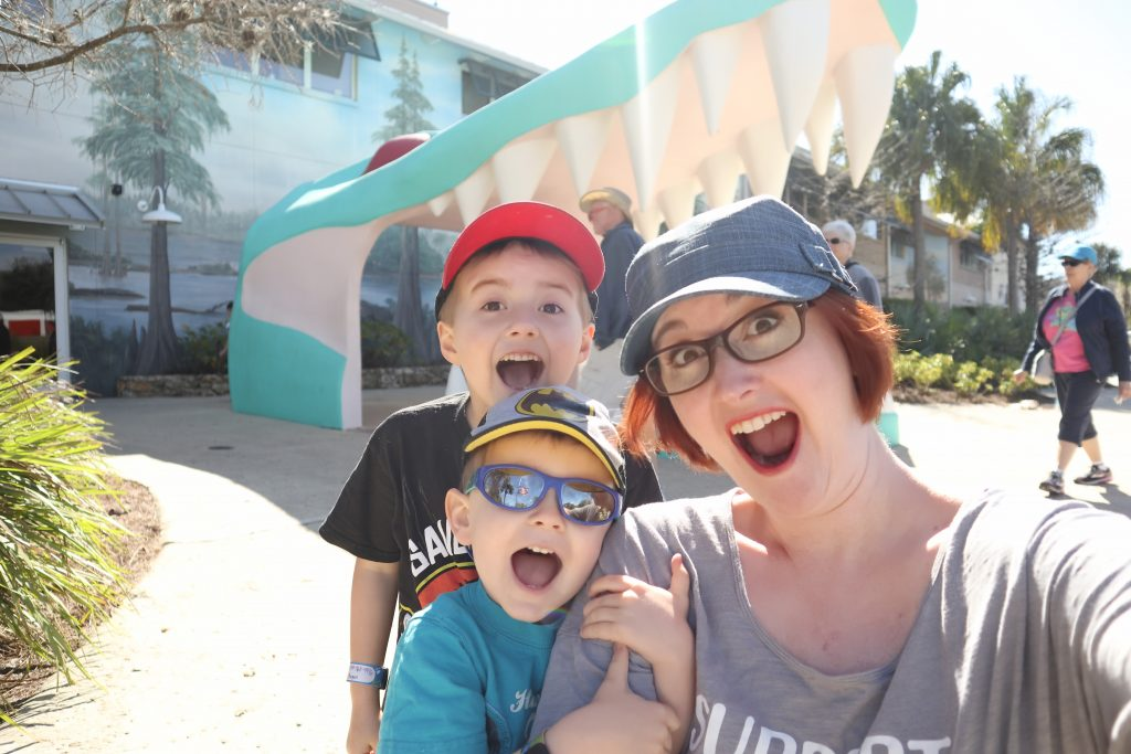 Mom with two little boys poses in front of the Gatorland teeth statue, acting scared