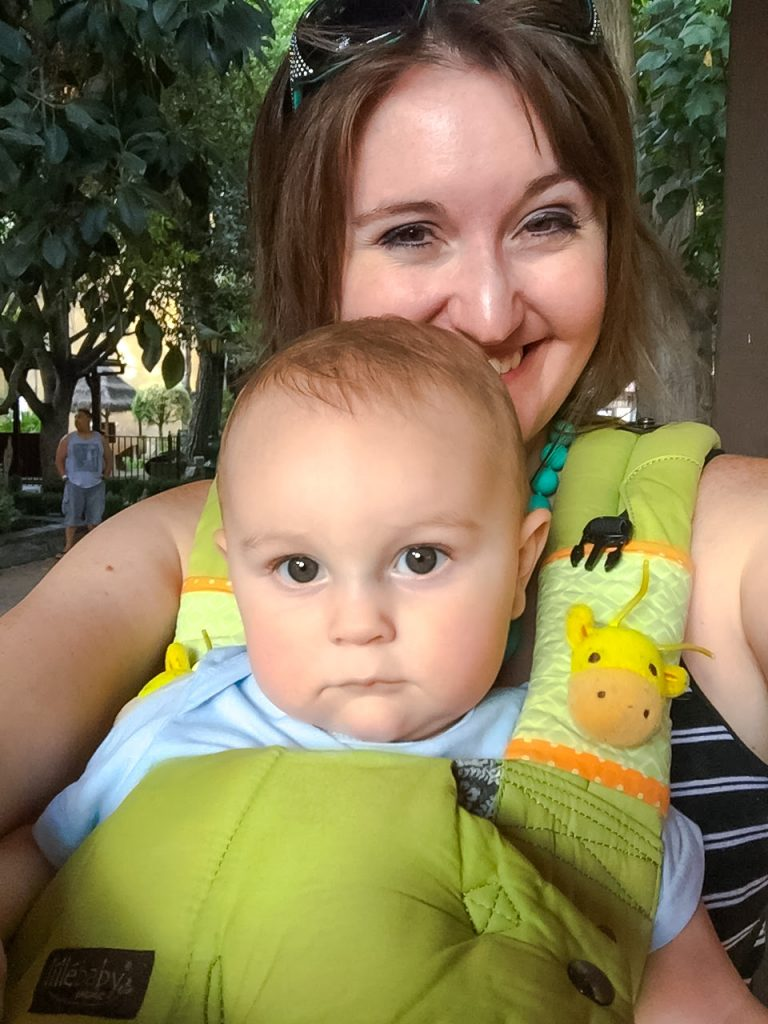 A chubby baby in a green Lillebaby Organic Complete carrier