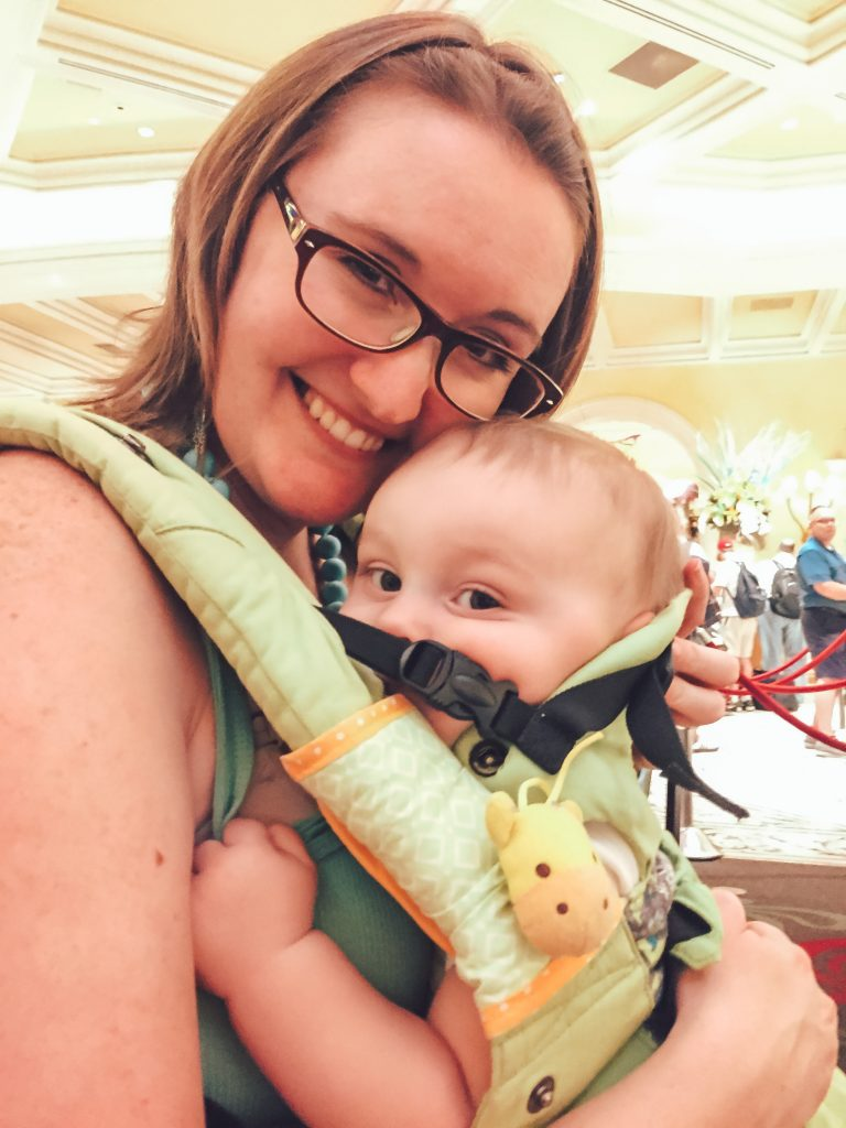 A happy baby and mom wearing a green Lillebaby Organic Complete baby carrier
