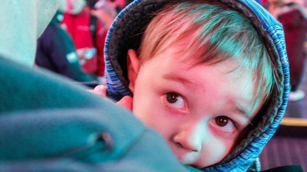 A toddler boy peeking his head over dad's shoulder, wearing a coat hood
