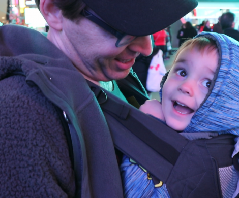 a happy little boy rides in his dad's Lillebaby baby carrier, looking at the lights of Times Square in New York City