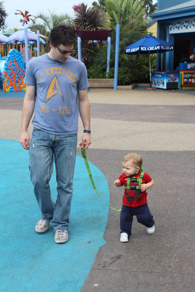 A dad and his toddler son, wearing a green backpack with a leash