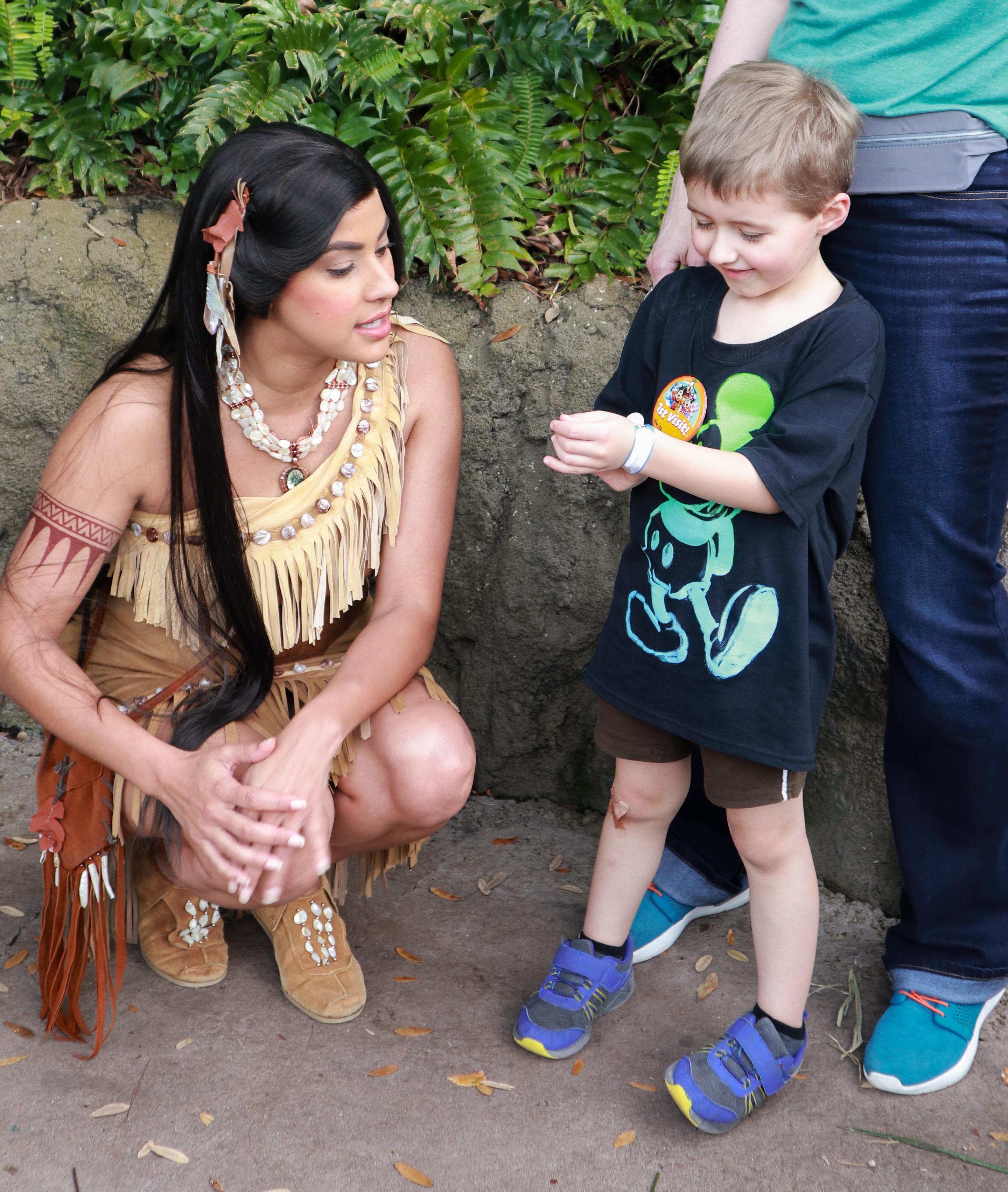 Pocahontas looks at a boy's ID bracelet