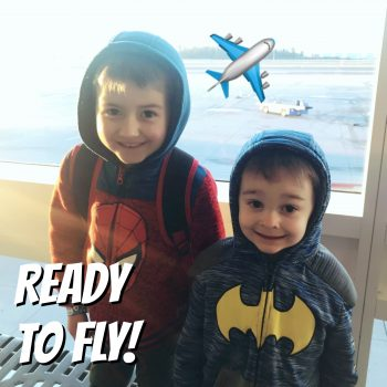 Two kids ready to fly on an airplane