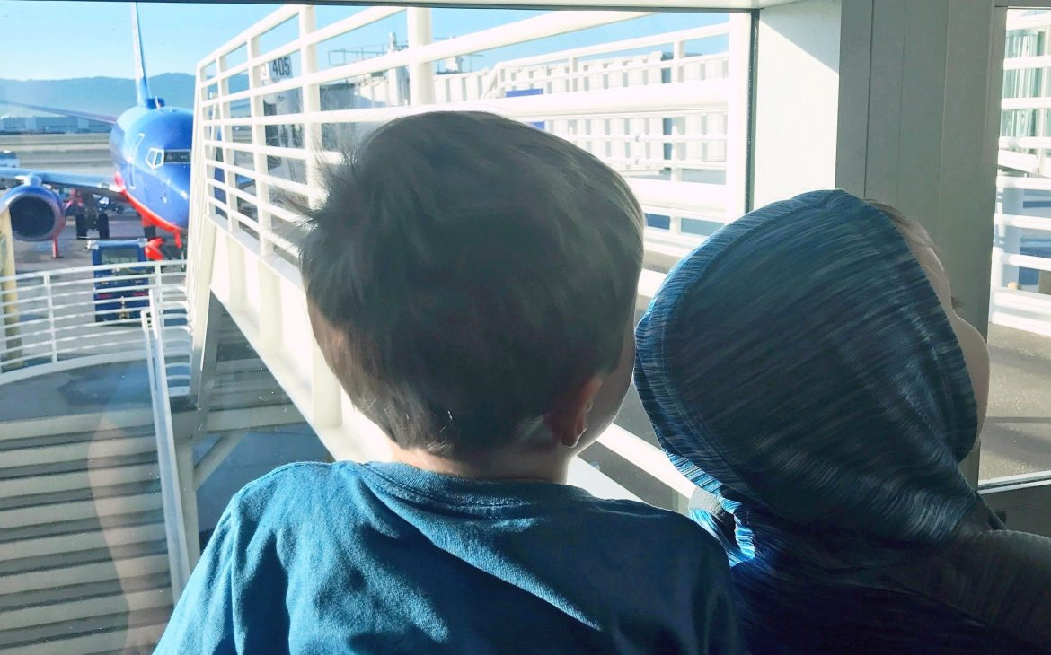 Two young kids look out a window at the airport terminal