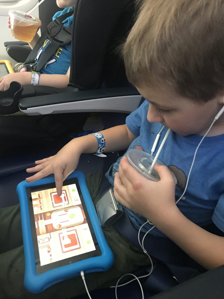 A boy plays with the Amazon Fire Tablet Kid Edition whle on an airplane