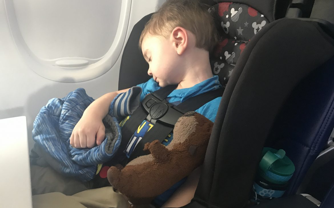 A little boy sleeps in his car seat on an airplane