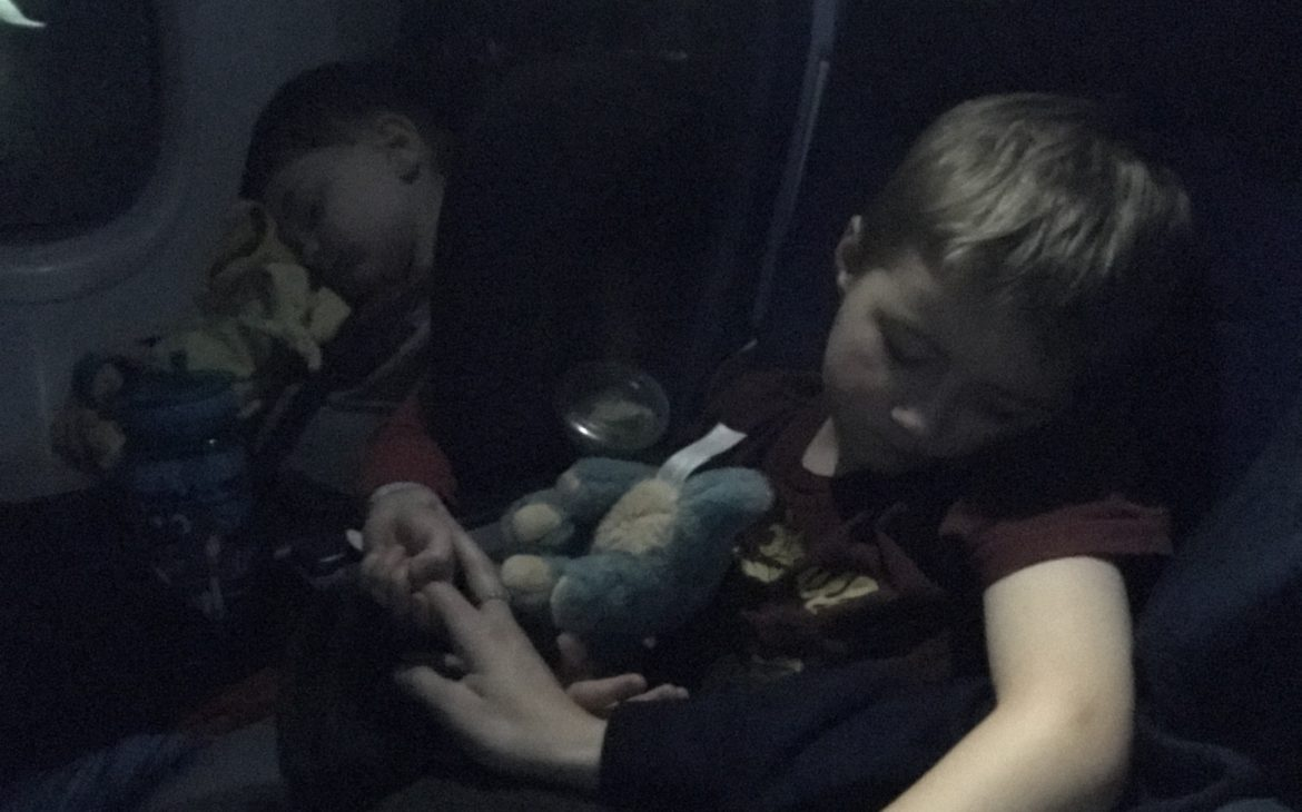 Two little boys sleeping on an airplane