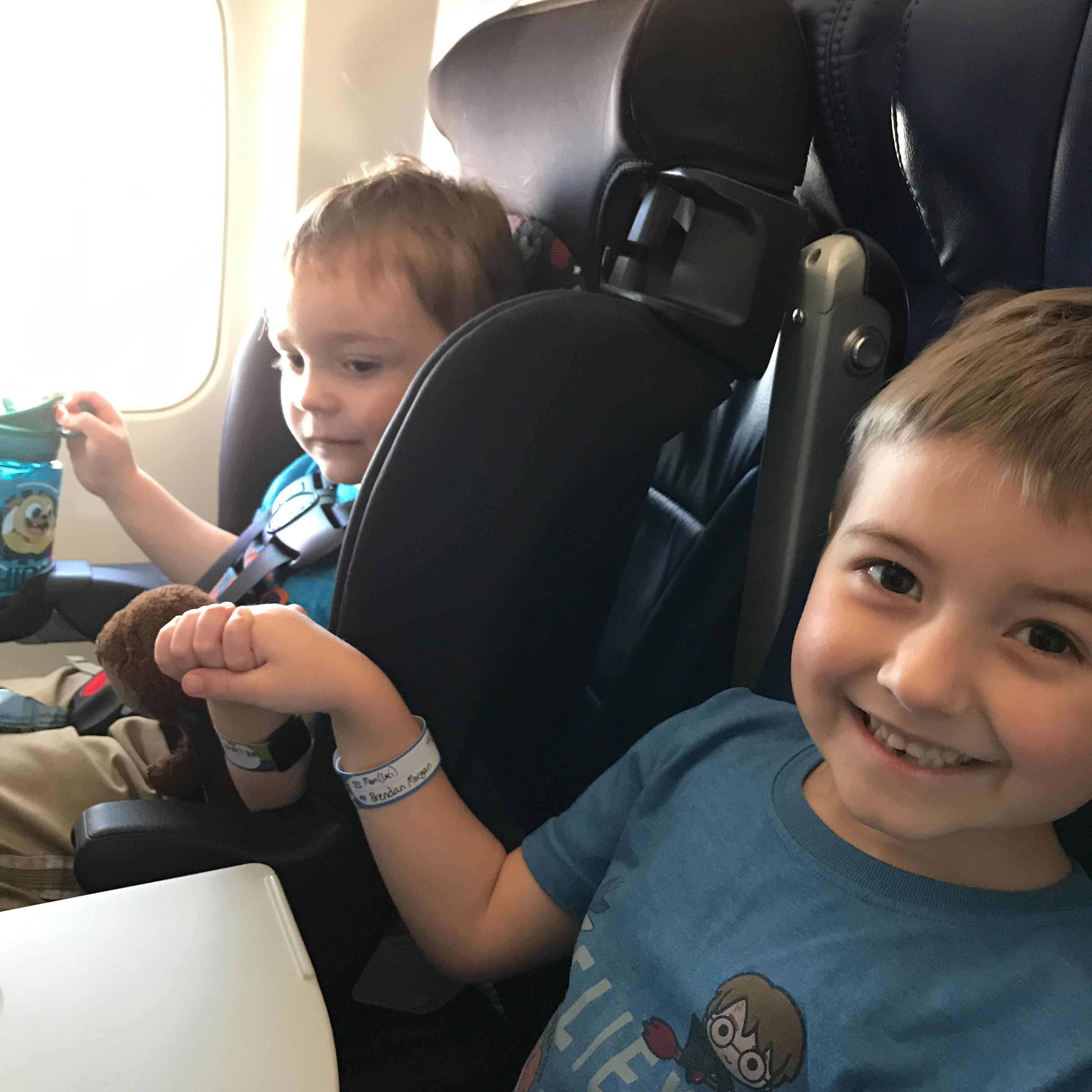 A kid holds his brother's hand on an airplane trip, flying with young kids
