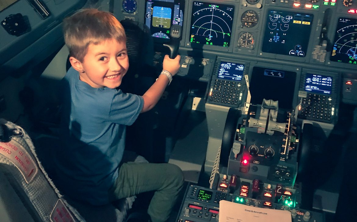 A happy little boy sitting in the pilot seat of a Southwest airplane, pretending to be the pilot