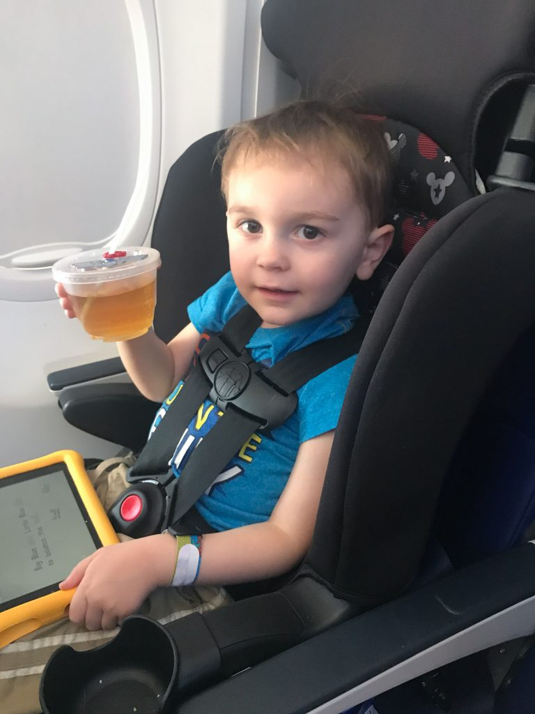 A little boy in a car seat on an airplane holds a cup of juice and a tablet on his lap