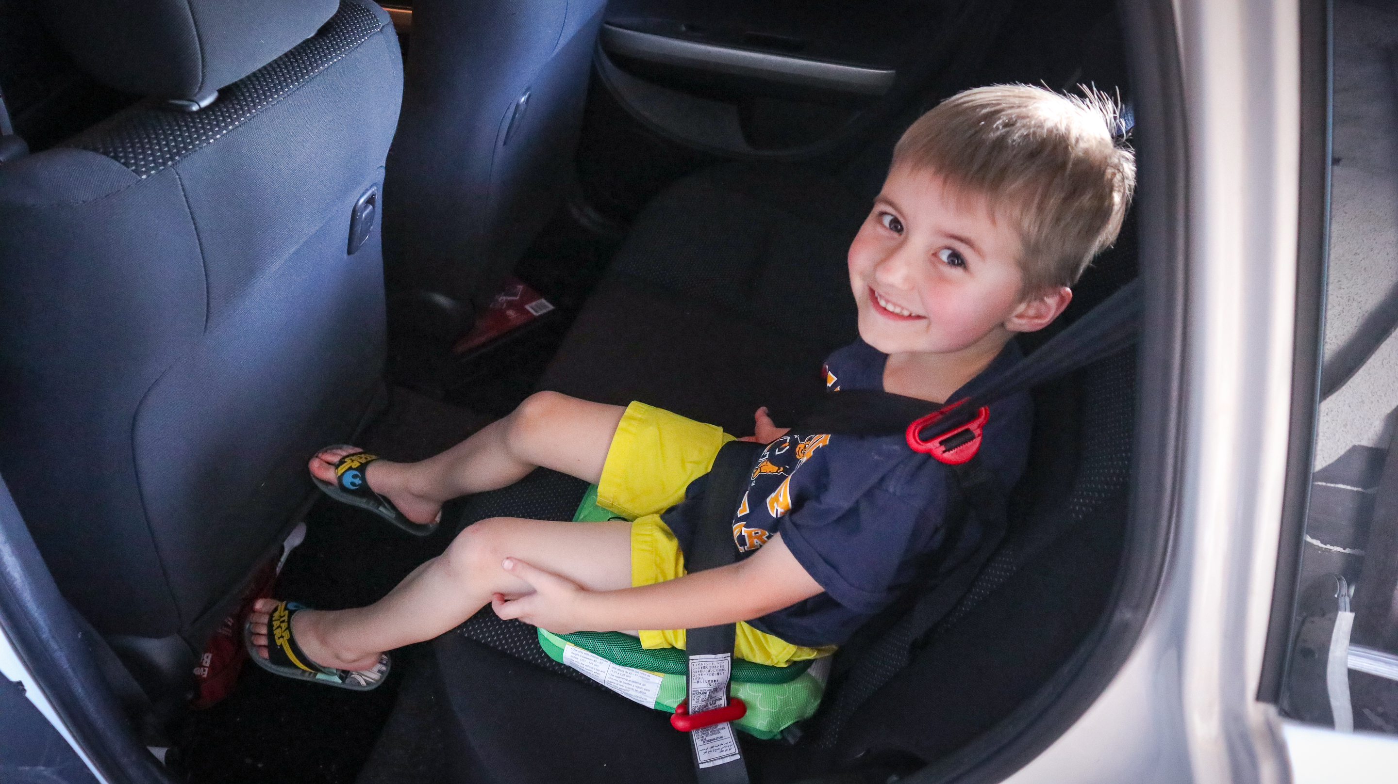 Six year old boy sitting in the back seat of a car, testing out the Bubblebum travel car seat