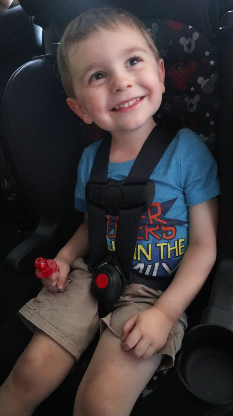A little boy smiling in his car seat