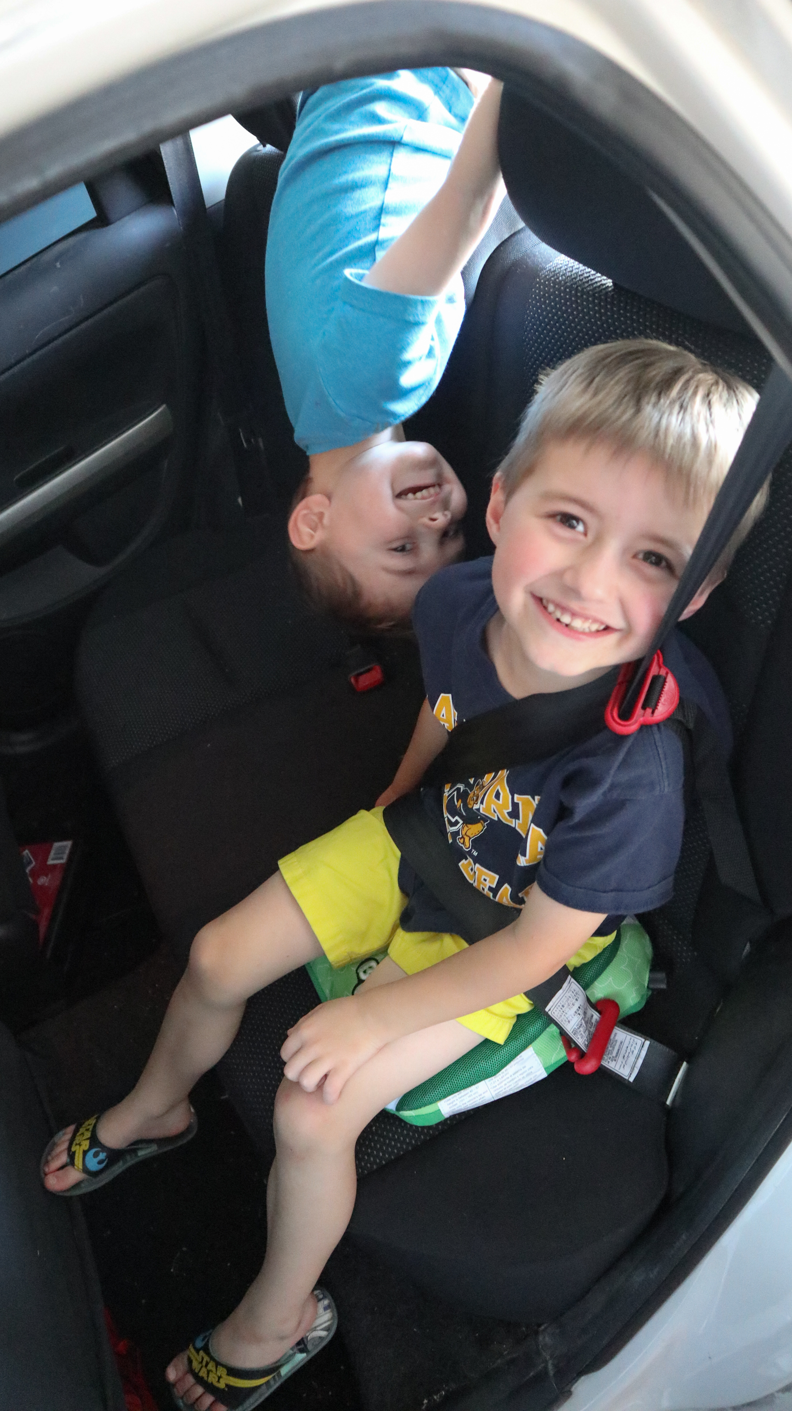Smiling boys playing in the backseat of a car, testing out the Bubblebum travel car seat