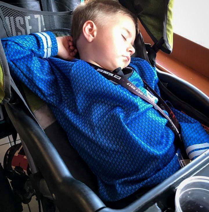 A little boy in a Spock Star Trek costume falls asleep in a stroller
