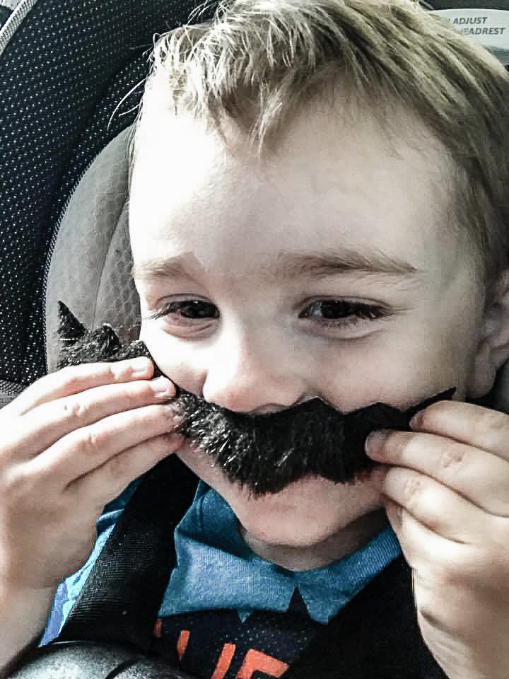 little boy holding up a fake Mario moustache