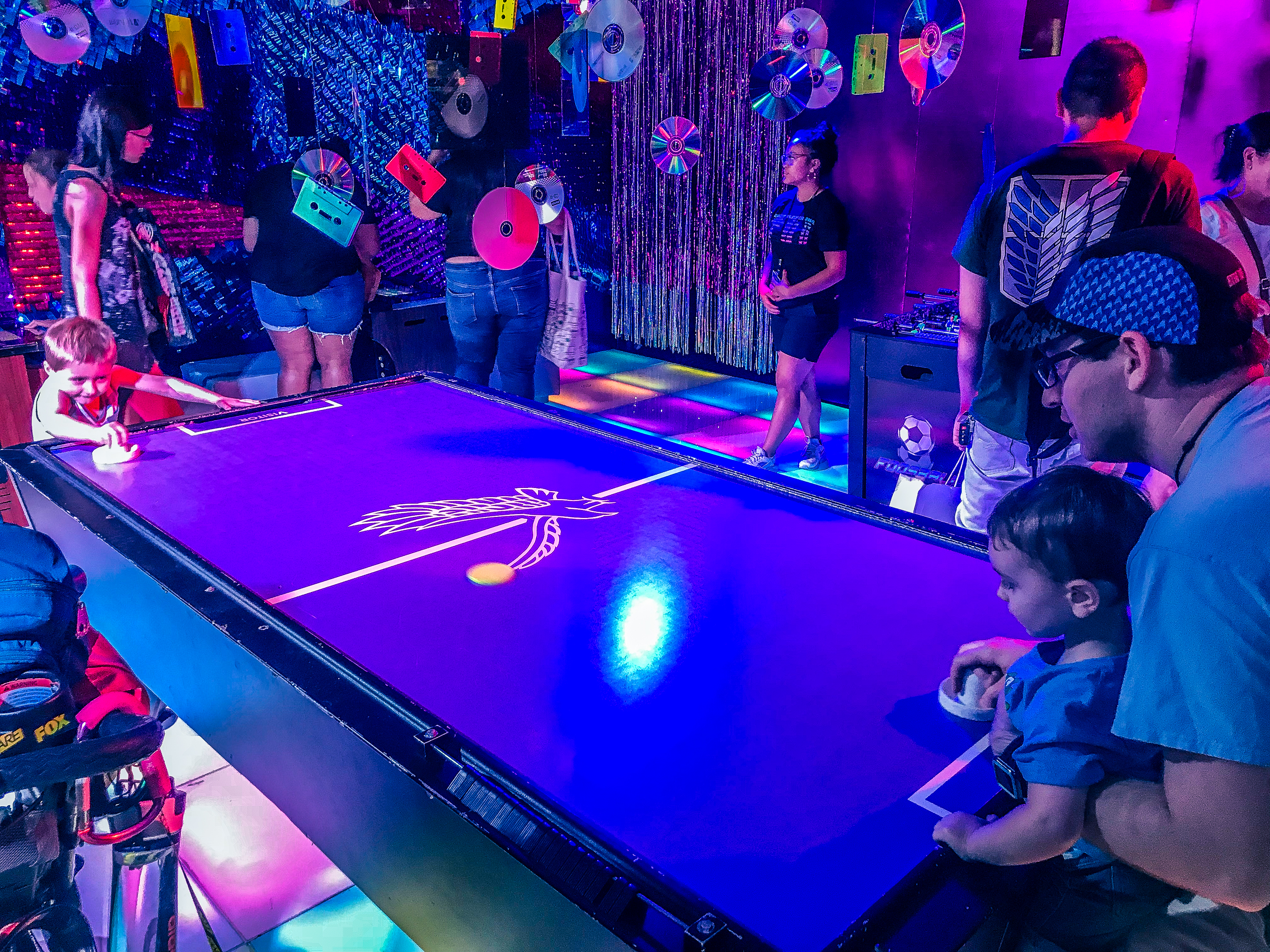 A family plays air hockey in a purple lit room, themed like Ready Player One at SDCC