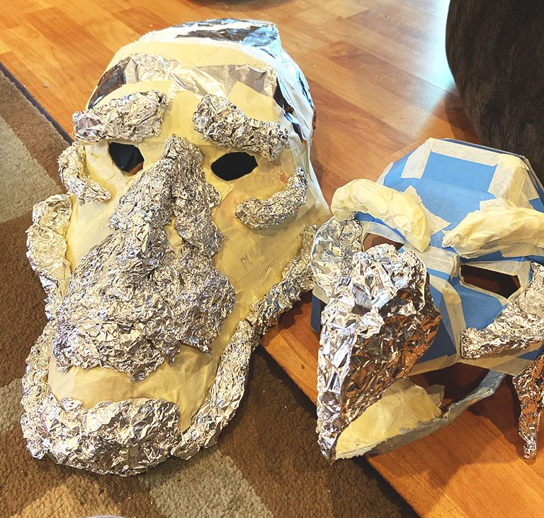 A Mystic and Skeksis mask from the Dark Crystal, made out of aluminum foil and cardboard